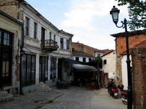 A street in the Old City, unusually empty of people, showing an old iron balcony.