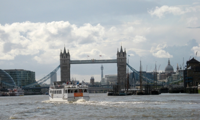 "Looking back upriver at Tower Bridge, heading down to Greenwich.  The river buses are catamarans; at one point they announced, ""This vessel will now travel at speed."" And it did. I do like messing about in boats, even as a passenger."